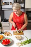Girl cutting onions in red dotted dress Royalty Free Stock Photo