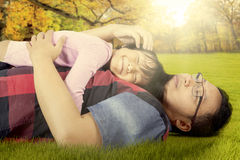 Cute girl and dad lying on the grass at park Stock Images