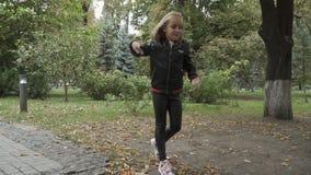 Cute girl dances ballroom dance in park in slowmotion stock footage