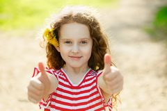 Cute girl with dandelion in her hairs, showing thumbs up. Royalty Free Stock Images