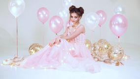 Cute girl with dark hair in a long light amazing pink dress, sitting on the floor in a bright garland surrounded by. Balls in studio on a white background stock footage