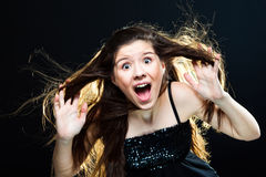 Cute girl with dark long hair shouting on black Stock Photography