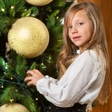 Cute girl decorating christmas tree. Stock Image