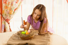 Cute girl decorating easter eggs in basket Stock Photos