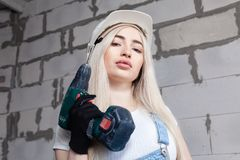 Cute girl designer foreman blonde in construction helmet in denim overalls holding cordless screwdriver. Ð¡oncept of repair in. The house, female labor, photo royalty free stock photos