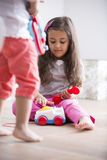 Cute girl dialing the toy telephone while playing with sister at home Royalty Free Stock Image