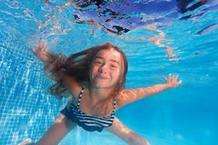 Cute girl diving under water of swimming pool. Underwater shoot of cute girl diving under clear water of swimming pool Royalty Free Stock Photography