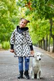 Beautiful young girl walking with dog outdoors. Pet concept. Cute girl with doggie walking in the park. Posing on the camera on the nature background. Full Royalty Free Stock Photos