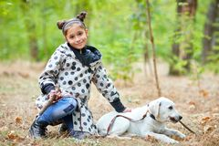 Beautiful young girl walking with dog outdoors. Pet concept. Cute girl with doggie walking in the park. Posing on the camera on the nature background. Full Royalty Free Stock Photo