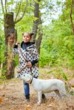 Beautiful young girl walking with dog outdoors. Pet concept. Cute girl with doggie walking and playing in the park. Posing on the camera on the nature Stock Images