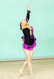 Cute girl doing crafty trick on art gymnastics performance. Indoors Royalty Free Stock Photography