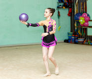 Cute girl doing crafty trick with ball on art gymnastics perform Stock Photos