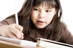 Cute girl doing homework. Mixed race girl doing homework over white background Royalty Free Stock Photos