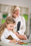 Cute girl doing homework while mother working. At home Royalty Free Stock Photo