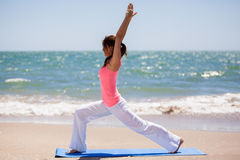 Cute girl doing some yoga. Pretty young woman practicing some yoga poses at the beach Stock Photography