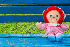 Cute girl doll sitting on a vintage bench Royalty Free Stock Photo