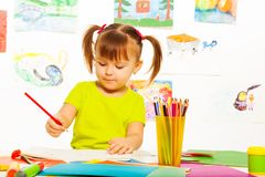 Cute girl draw with pencil. Cute little 3 years old girl in yellow shirt and pony tails draw with pencil in the art class with images on the wall Royalty Free Stock Image