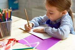 Cute Girl Drawing in Art Class. Portrait of cute little girl drawing picture at desk in art class, copy space royalty free stock image