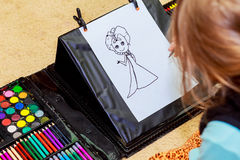 Cute girl drawing with colourful pencils Royalty Free Stock Photos