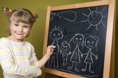 Cute girl drawing family Royalty Free Stock Photography