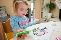 Cute girl drawing a fish using glass colors at home.
