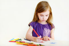 Cute girl drawing a picture with colorful pencils Royalty Free Stock Image