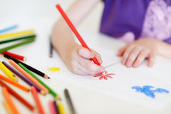 Cute girl drawing a picture with colorful pencils Stock Image