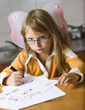 Cute girl drawing pictures. Cute young girl with angel wings drawing pictures on table royalty free stock photos