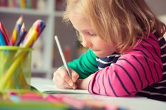 Cute girl drawing at school. Cute pretty girl drawing with pencils at school royalty free stock photo
