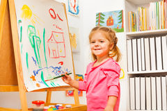 Cute girl is drawing using a brush at easel Royalty Free Stock Photo