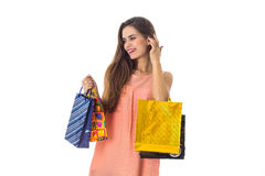 Cute girl in dress keeps on hand a different shopping bags isolated  white background Stock Images