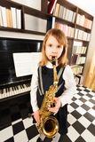 Cute girl in dress plays on the alto saxophone Stock Photo