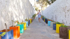 Cute girl in dress at street of typical greek traditional village with white walls and colorful doors on Mykonos Island. Girl in blue dresses having fun outdoors stock video footage