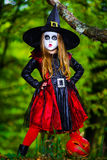 Cute girl dressed to Halloween costume in dark forest. Holiday concept Stock Image