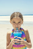 Cute girl drinking a blue ice drink at the beach during summer vacation Stock Photo