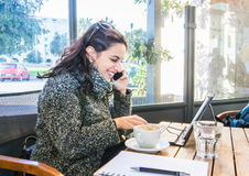 Cute girl drinking cappuccino, talking on the phone and writing on a tablet Stock Photography