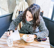 Cute girl drinking cappuccino and writing on a notebook - front view Stock Photography