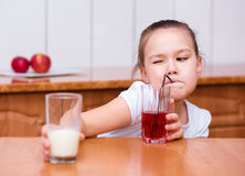 Cute girl is drinking cherry juice Stock Photo