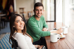 Cute girl drinking coffee with a guy. Portrait of a gorgeous young Hispanic brunette relaxing and having some coffee with a guy in a cafe Stock Photography