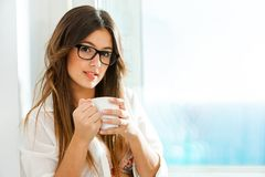 Cute girl drinking coffee at window. Stock Images