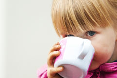 Cute girl drinking from cup stock photography