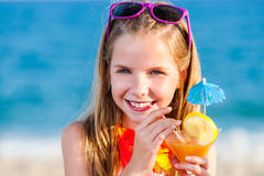 Cute girl drinking fruit cocktail on beach. Stock Photos