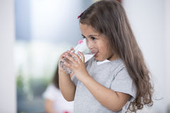 Cute girl drinking glass of water at home