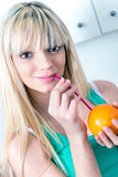 Cute girl drinking an orange from a straw Royalty Free Stock Photos