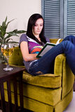 Cute Girl Drinking while Reading a Book Royalty Free Stock Image