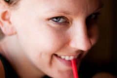 Cute girl drinking a soda. This cute young woman smiles at the camera as she sips from her drink royalty free stock photo