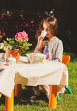 Cute girl drinking tea at toy table at yard Stock Image