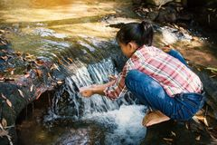 Cute girl drinking water from waterfall stream Royalty Free Stock Photo