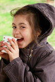 Cute girl drinks coffee in cold weather. Cute girl drinks coffee in a park in cold weather stock photography