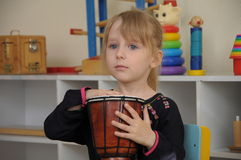 Cute girl drumming in kindergarten Royalty Free Stock Image